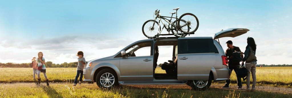 Dodge Grand Caravan in a field with a family around it and bikes on top