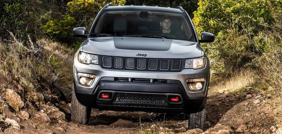 2019 Jeep Compass Trailhawk in Billet Metallic driving through mud in an off-road trench towards the camera