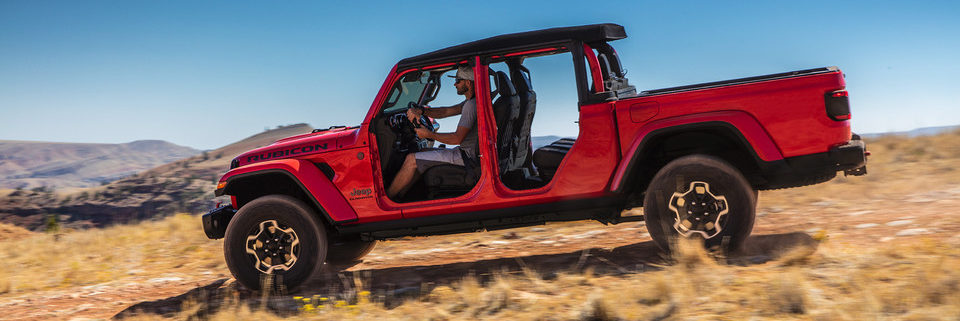 Side exterior of 2020 Jeep Gladiator driving down a hill