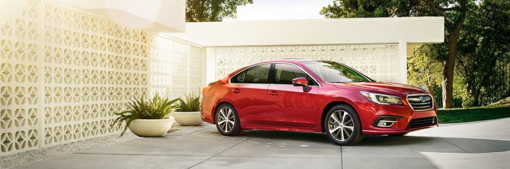 2019 Subaru Legacy 3.6R Limited with EyeSight technology, in Crimson Red Pearl, parked in driveway next to 2 potted leafy plants