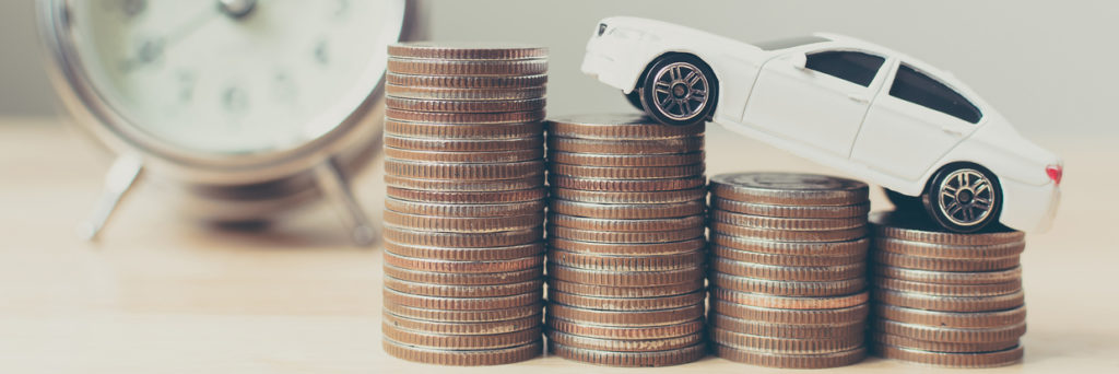 miniature car on coin stack