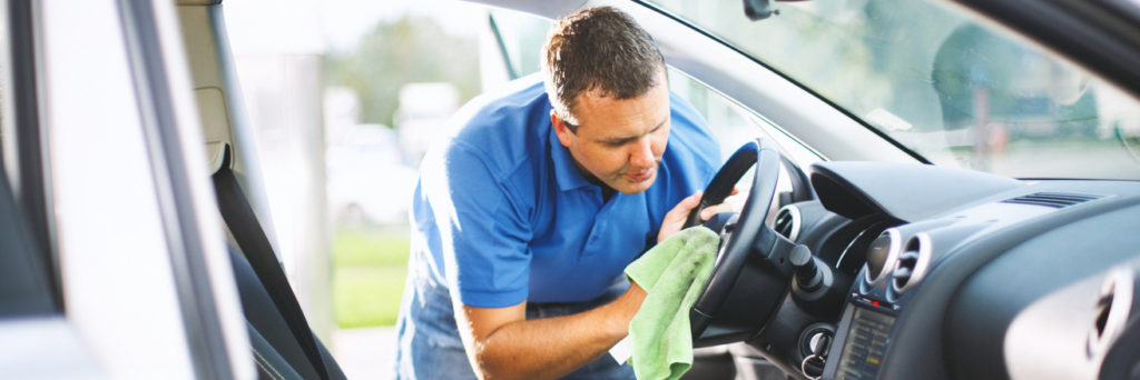 Man cleaning a steering wheel with a cloth