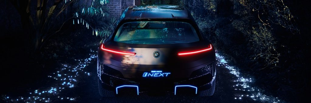 Rear night time shot of BMW iNext, illuminated iNext in light blue on vehicle bumper