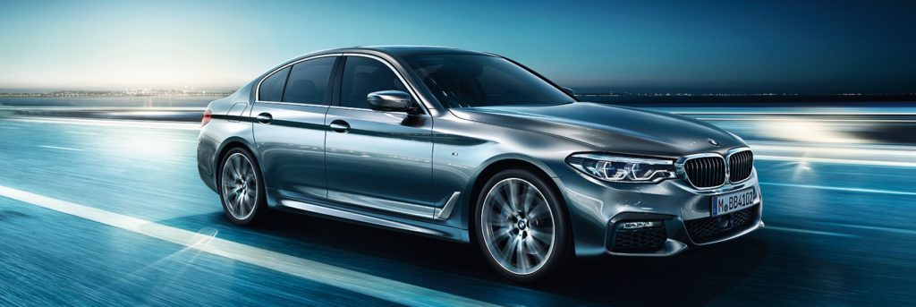 BMW 5 Series sedan driving through futuristic road