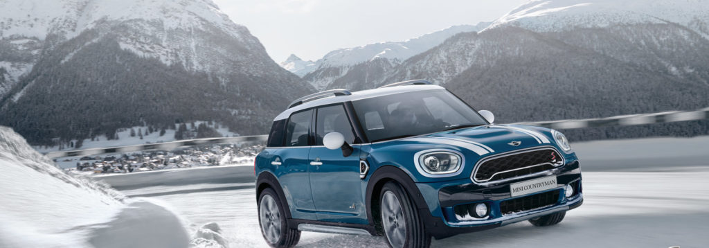blue mini driving on a snowy road around a corner