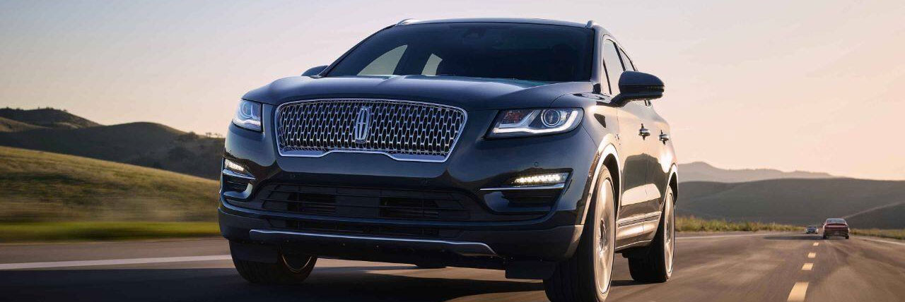 2019 Lincoln MKC is shown being driven on a long stretch of country road with lush green hills in the background