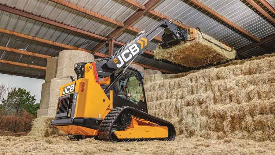 Rear 3/4 view of a JCB machine loading hay stacks on top of each other