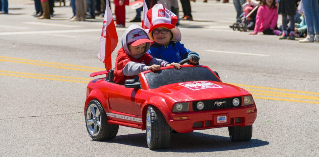 Chicago, IL, United States - May 06, 2017: Young children parading in a toy car during The Polish Consitution Day Parade in Chicago.