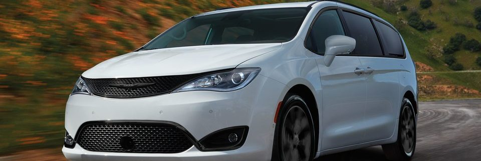 2019 white Chrysler Pacifica driving by two grassy hills