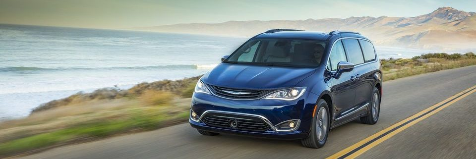 Chrysler Pacifica Hybrid driving on a road near a body of water