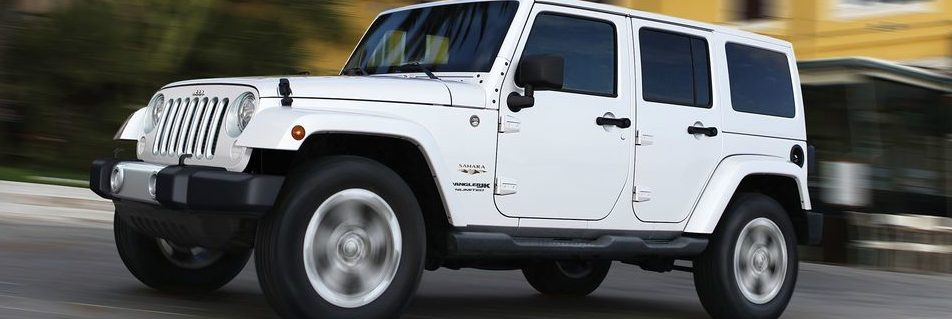 Jeep Wrangler JK white exterior driving on a city road