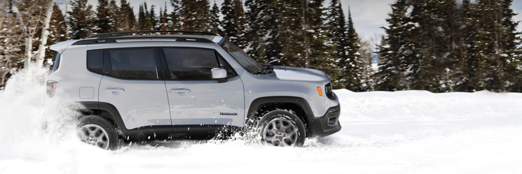 Jeep Renegade driving through a snowy field
