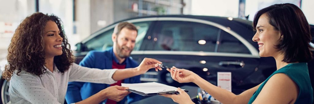 Two smiling women exchange keys and a contract during a car sale, while a smiling man looks on in the background