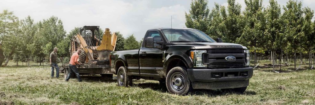 Super Duty XL regular cab shown in Agate Black towing a loader