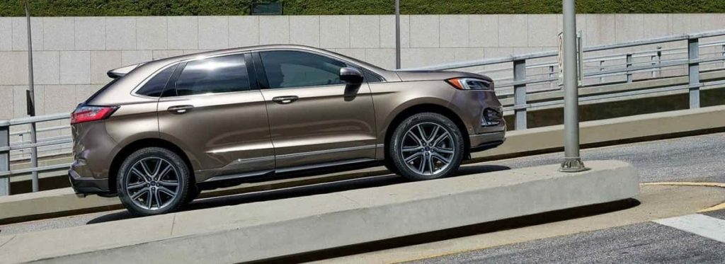2019 Ford Edge in shiny tan stopped on a slanted road