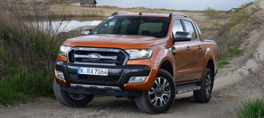 Brand-new Ford Ranger in orange parked on a dirt road with a lake in the background