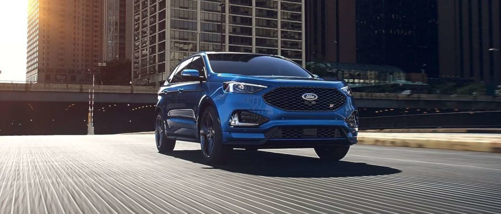 The 2019 Ford Edge ST in performance Blue driving on a city bridge with the sunset glaring in the top left corner