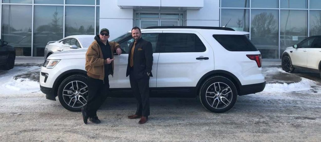 Pete Potipcoe and Jamia Jasmin posing in front of a white 2019 Ford Explorer Sport