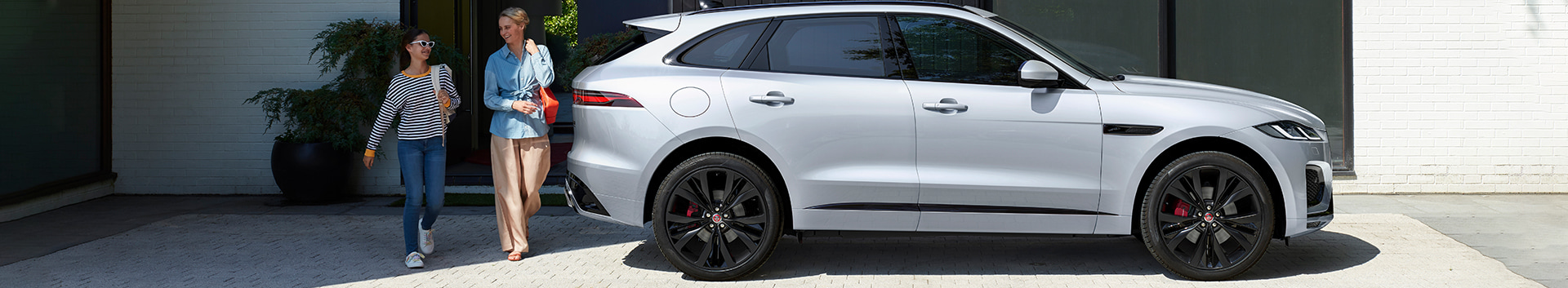 Side exterior view of the 2021 Jaguar F-Pace parked outside of a home