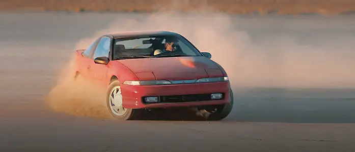 A red Mitsubishi Eclipse on a dirt road