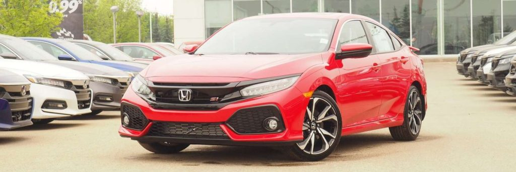 A red Honda Civic Si parked in front of an Alberta Honda dealership