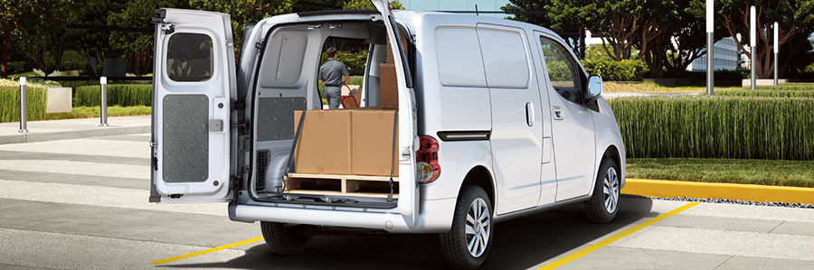 NV200 compact shown in white with rear doors open, large brown box strapped down in cargo hold