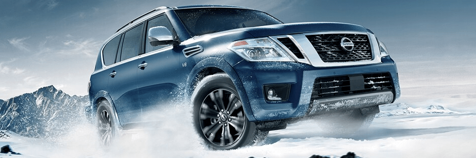 2020 Nissan Armada shown in Hermosa Blue, driving through snow and ice, rocky terrain in background
