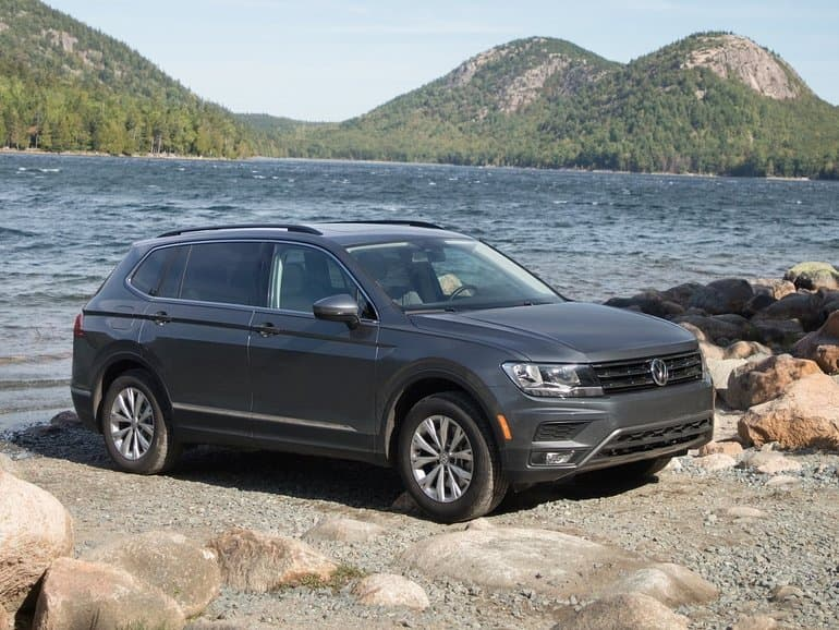Side exterior view of the 2018 Volkswagen Tiguan parked on the edge beside a river