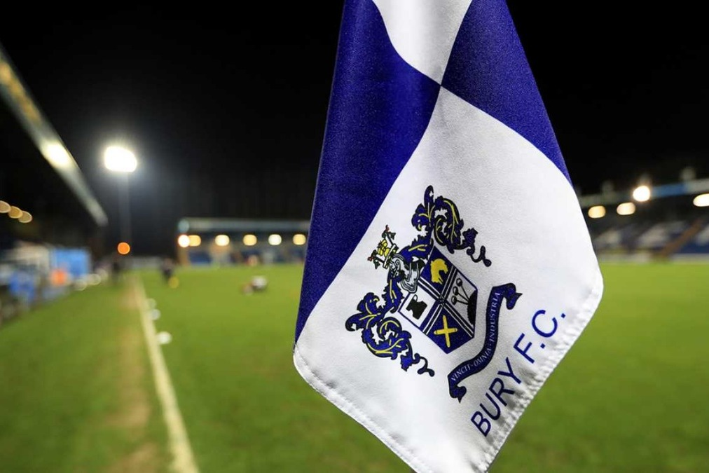 A picture of the Bury FC crest on a corner flag overlooking Gigg Lane, their stadium.