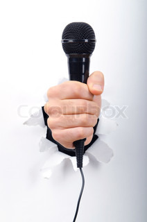 Hand Holding Microphone Through Hole In Paper Stock