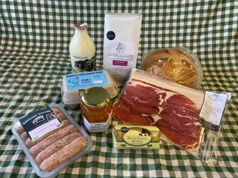A Breakfast Box: bringing together produce from eight local producers. white cob, butter, coffee, milk, marmalade, eggs, sausages and bacon.