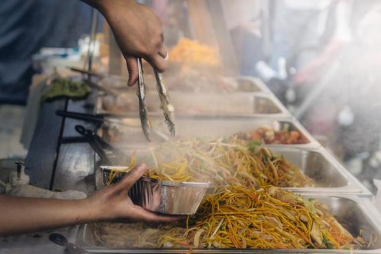 食品のビュッフェを提供するベンダー市場のパスタの手は煙