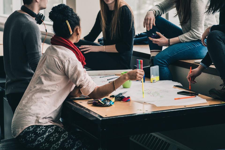 人々の女の子の女の子の友人男の子話す会議の研究グループ活動の宿題カラフルなペン描画描画青写真紙のテーブル