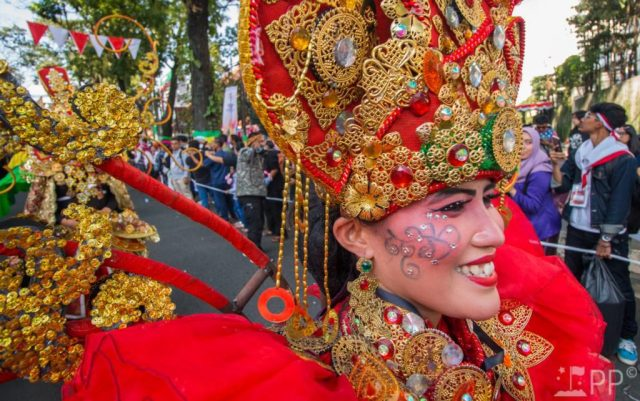Costumed women with red fabric, and gold accessories