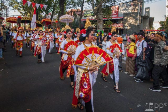 Women dressed in red and white with matching fans, and accents of gold to represent Bali