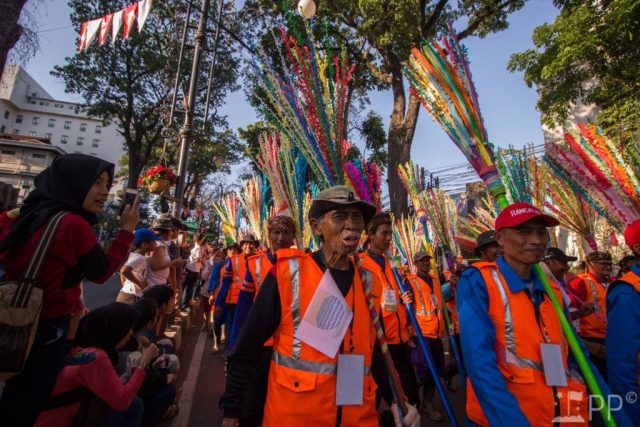 Workers in bright orange vests with multi-colored fake brooms