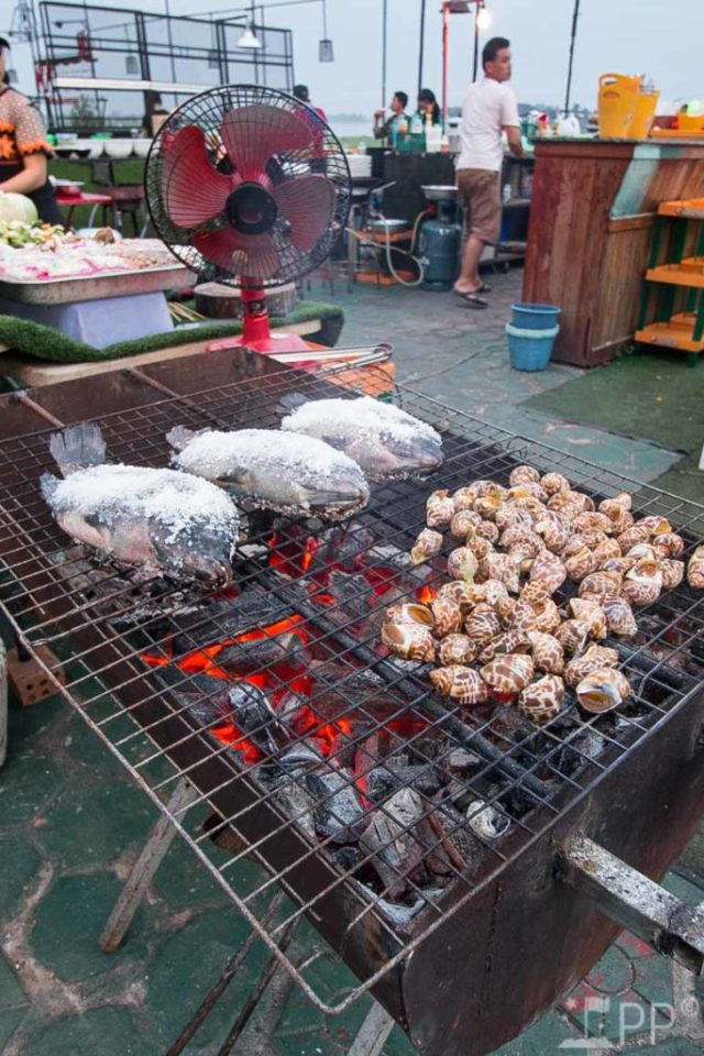 Open charcoal grill with salted fish and snails