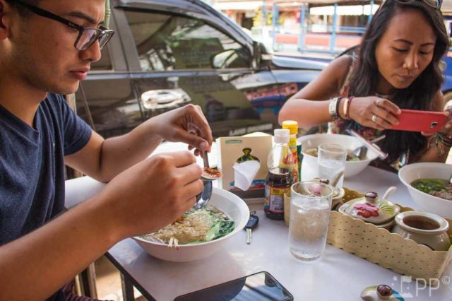 Two people enjoy their fresh batch of soup.