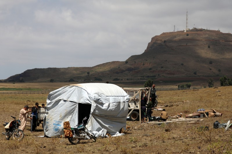 Internally displaced people from Deraa province erect a tent near the Israeli-occupied Golan Heights in Quneitra