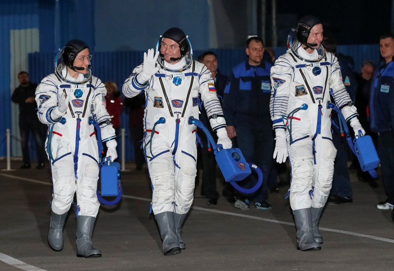 The International Space Station (ISS) crew members walk shortly before leaving to board the spacecraft at the Baikonur Cosmodrome