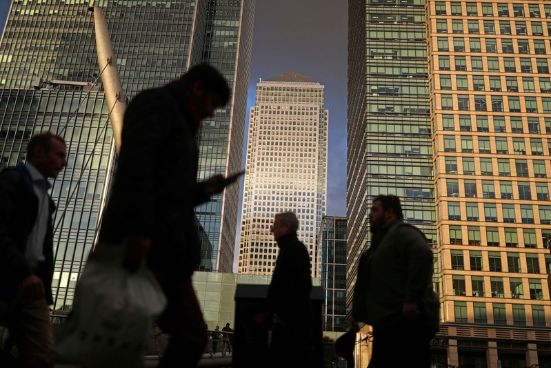 FILE PHOTO: People walk through the Canary Wharf financial district of London