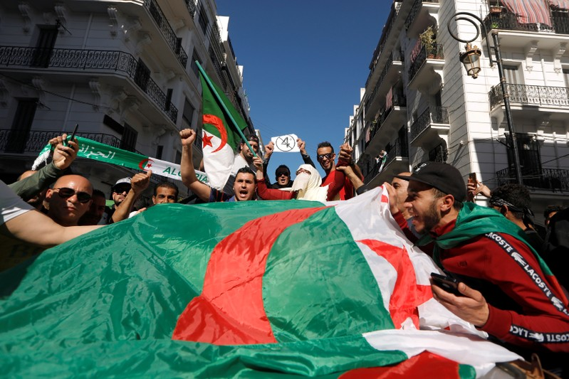 People carry their national flags as they protest over President Abdelaziz Bouteflika's decision to postpone elections and extend his fourth term in office, in Algiers