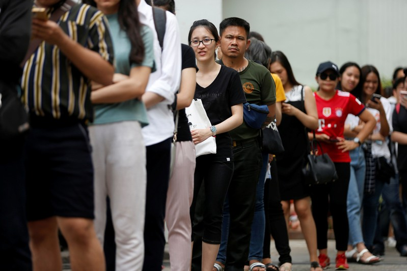 People like up for their early vote for the upcoming Thai election at a polling station in Bangkok