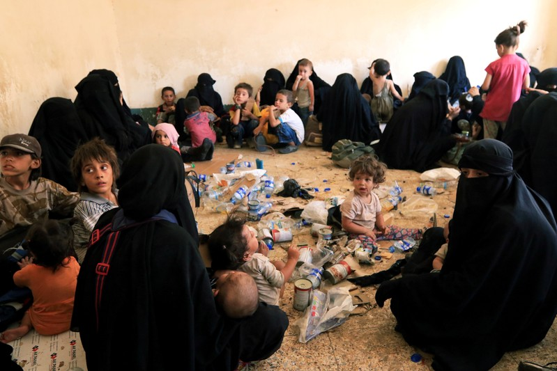 FILE PHOTO: Families and relatives of Islamic State militants are seen after they surrender themselves to the Kurdish Peshmerga forces in al-Ayadiya, northwest of Tal Afar