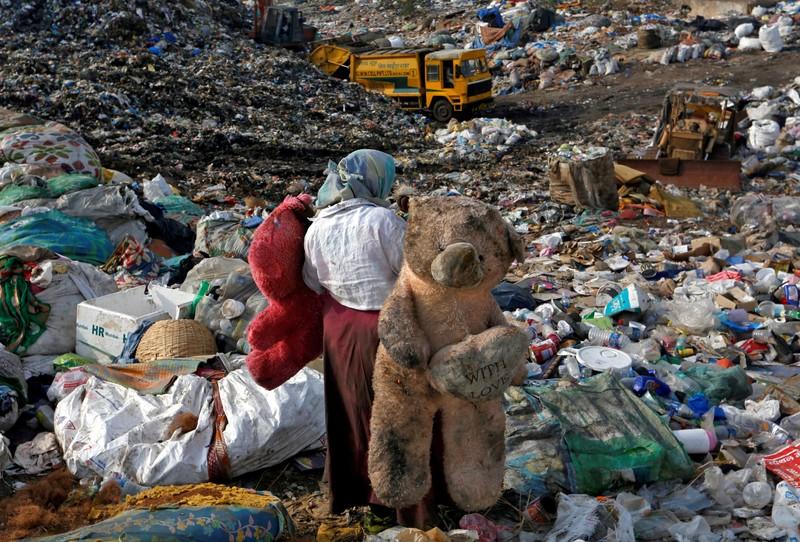 FILE PHOTO: Woman carries stuffed toys through a dump site in Mumbai