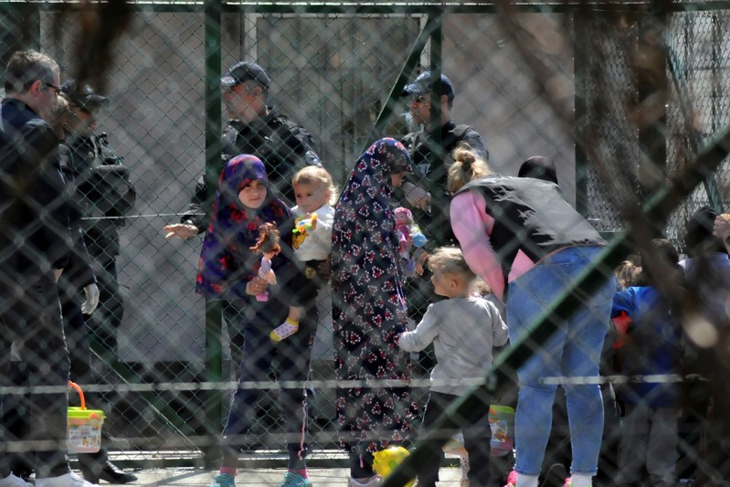 Police officers guard women and children who are relatives of Kosovo Jihadists who returned from Syria, at foreigners detention centre in Pristina