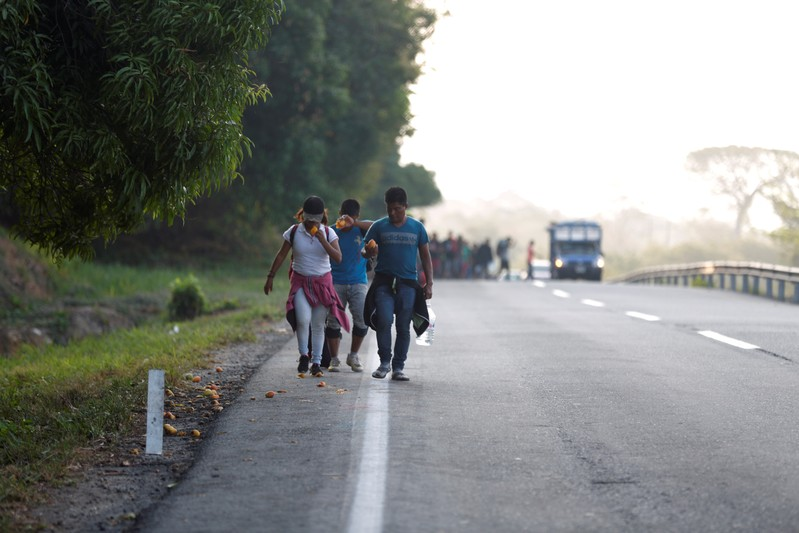 Central American migrants eat mangoes for breakfast as they walk during their journey towards the United States, in Mapastepec