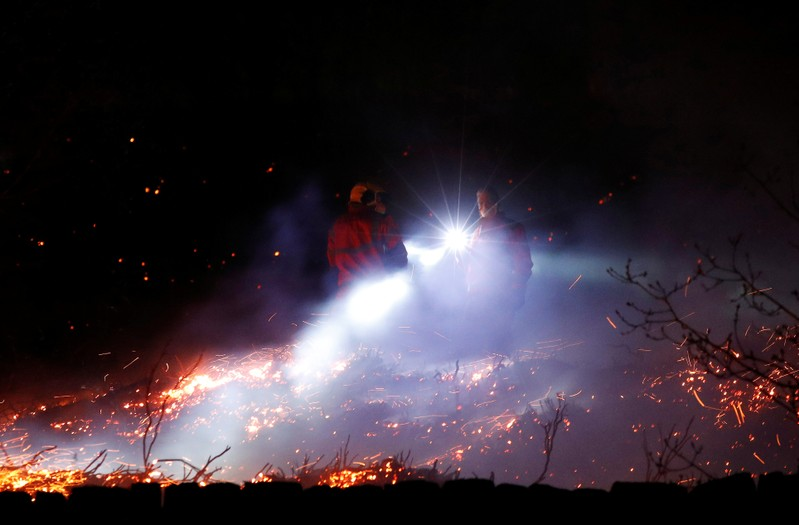 Firefighters tackle a fire on a patch of moorland above the village of Uppermill