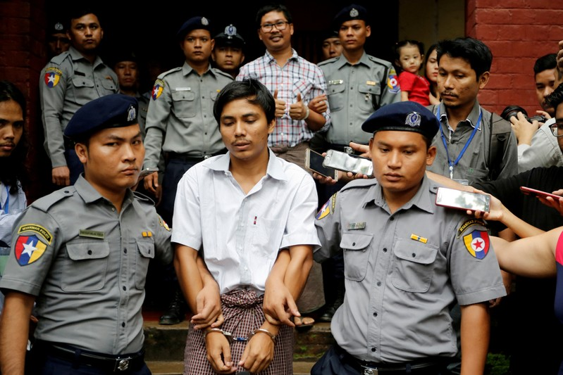 FILE PHOTO: Detained Reuters journalist Kyaw Soe Oo and Wa Lone are escorted by police as they leave after a court hearing in Yangon