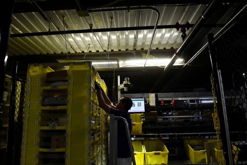 Worker takes products for delivery from a robotic shelf at the Amazon fulfilment center in Baltimore
